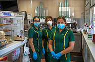 Serving Cuban coffee and pastelitos, Ramona Duran, Nina Porras and Marivel Gutierrez pause for a photograph while wearing protective masks and gloves at La Ventanita at the popular Versailles Cuban restaurant now open for take out service only during the COVID19 pandemic in Miami on Wednesday, April 1, 2020.