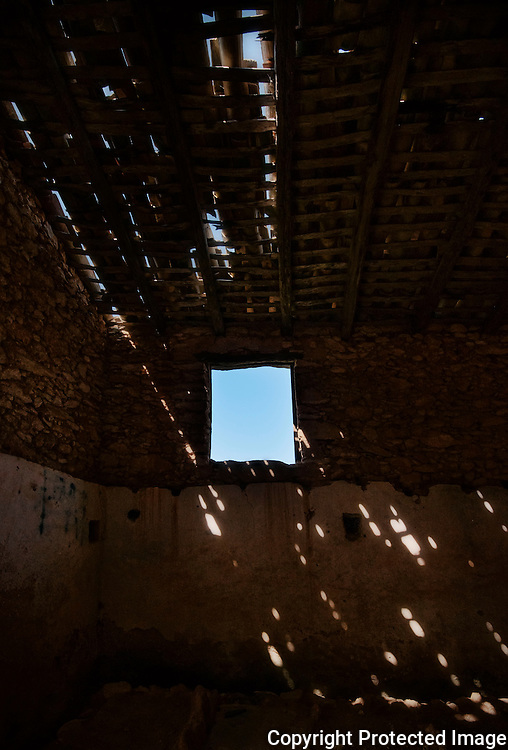 Light beams passing through a rotten roof of a once were farmers house.