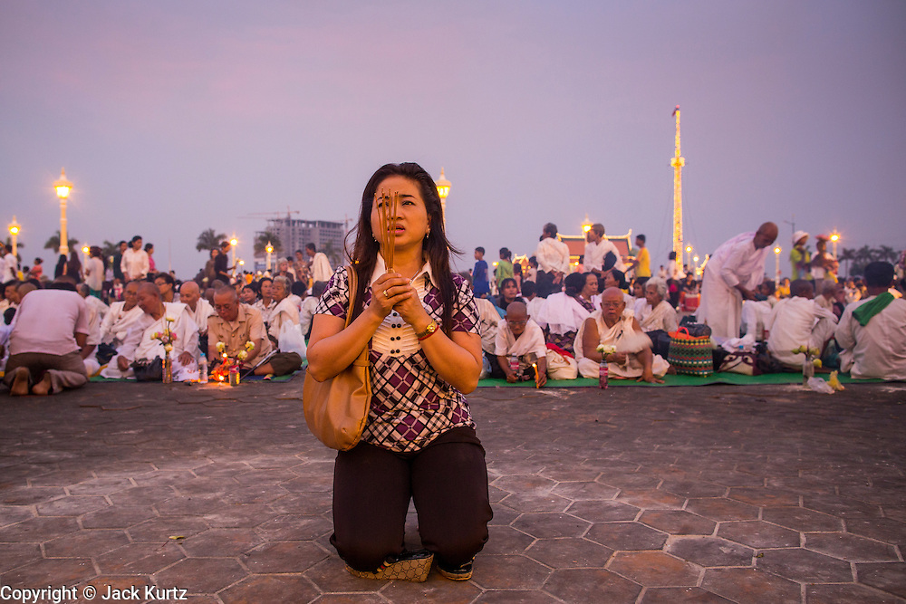 """29 JANUARY 2013 - PHNOM PENH, CAMBODIA:   A woman prays for late Cambodian King Norodom Sihanouk on the plaza in front of the Royal Palace in Phnom Penh. Sihanouk (31 October 1922- 15 October 2012) was the King of Cambodia from 1941 to 1955 and again from 1993 to 2004. He was the effective ruler of Cambodia from 1953 to 1970. After his second abdication in 2004, he was given the honorific of """"The King-Father of Cambodia."""" Sihanouk held so many positions since 1941 that the Guinness Book of World Records identifies him as the politician who has served the world's greatest variety of political offices. These included two terms as king, two as sovereign prince, one as president, two as prime minister, as well as numerous positions as leader of various governments-in-exile. He served as puppet head of state for the Khmer Rouge government in 1975-1976. Most of these positions were only honorific, including the last position as constitutional king of Cambodia. Sihanouk's actual period of effective rule over Cambodia was from 9 November 1953, when Cambodia gained its independence from France, until 18 March 1970, when General Lon Nol and the National Assembly deposed him. Upon his final abdication, the Cambodian throne council appointed Norodom Sihamoni, one of Sihanouk's sons, as the new king. Sihanouk died in Beijing, China, where he was receiving medical care, on Oct. 15, 2012. His cremation is scheduled to take place on Feb. 4, 2013. Over a million people are expected to attend the service.     PHOTO BY JACK KURTZ"""