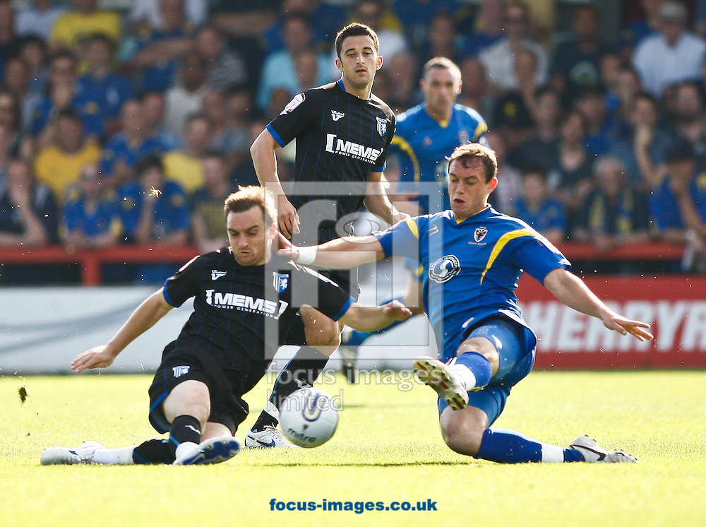 Picture by Andrew Tobin/Focus Images Ltd. 07710 761829. .1/10/11. Charlie Lee (4) of Gillingham (L) and Luke Moore (11) of AFC Wimbledon (R) challenge for a loose ball during the .Npower League 2 match between AFC Wimbledon and Gillinghamat at The Cherry Red Records Fans' stadium, Kingsmeadow, London.