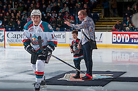 KELOWNA, CANADA - DECEMBER 27: Jake Kryski #14 of the Kelowna Rockets skates to the bench after being awarded player of the month and earning a new suit from Wayne McDermott of McDermott's on Bernard on December 27, 2016 at Prospera Place in Kelowna, British Columbia, Canada.  (Photo by Marissa Baecker/Shoot the Breeze)  *** Local Caption ***