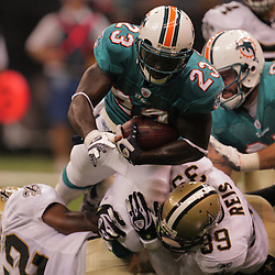 2008 August 28: Ronnie Brown (23) of the Miami Dolphins is tackled by Saints defenders Chris Reis (39) and William Kenshaw (52) during a preseason match up at the Louisiana Superdome in New Orleans, LA.