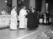 Episcopal Ordination Of Desmond Connell. (R74).1988..06.03.1988..03.06.1988..6th March 1988..Following the death of Archbishop Kevin McNamara in April '87, Pope John Paul II surprisingly nominated Desmond Connell for the position of Archbishop of Dublin. The ordination of Dr Connell took place at the Pro-Cathedral in Dublin...Archbishop Desmond Connell is pictured accepting the bread and wine from two nuns as he prepares to say his first mass as Archbishop of Dublin.