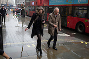Two Londoners carry their precious coffees during a downpour in Piccadilly, on 3rd December 2018, in London, UK