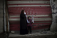 A girl stands with a woman holding a white flag as they flee their homes during fighting between Iraqi security forces and Islamic State militants, on the western side of Mosul, Iraq, Monday, March 13, 2017. (AP Photo/Felipe Dana)