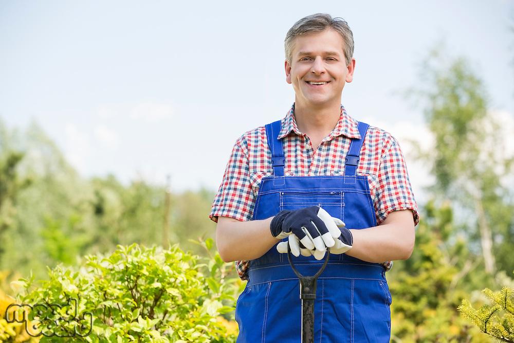 Portrait of happy gardener holding spade in plant nursery