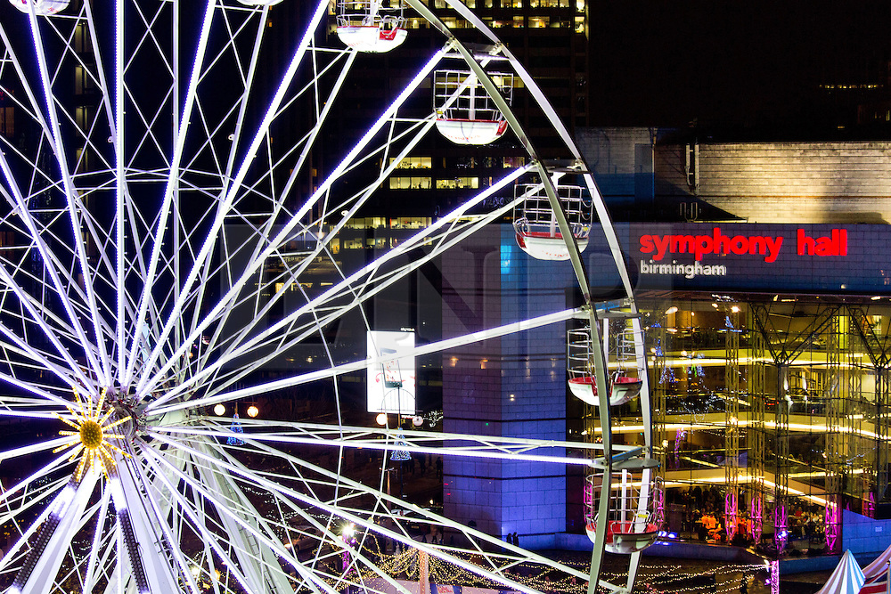 © Licensed to London News Pictures. 29/11/2013. Birmingham, UK. Birmingham Frankfurt Market. Pictured, the ferrris wheel seems to dwarf Symphony Hall in Milennium Square. Birmingham hosts the largest outdoor Market in the Country every year. The annual Frankfurt German Market, has visited Birmingham for the last 12 years and is bigger than ever before this year. The market has even more stalls, 190 in total. An ice rink and ferris wheel complete the winter wonderland that draws thousands to the city centre over the build up Christmas. Photo credit : Dave Warren/LNP