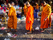 "04 DECEMBER 2018 - BANGKOK, THAILAND:  Buddhist monks walk through a market street cluttered with discarded single use plastic bags in Khlong Toei market. The issue of plastic waste became a public one in early June when a whale in Thai waters died after ingesting 18 pounds of plastic. In a recent report, Ocean Conservancy claimed that Thailand, China, Indonesia, the Philippines, and Vietnam were responsible for as much as 60 percent of the plastic waste in the world's oceans. Khlong Toey (also called Khlong Toei) Market is one of the largest ""wet markets"" in Thailand. December 4 was supposed to be a plastic free day in Bangkok but many market venders continued to use plastic.     PHOTO BY JACK KURTZ"