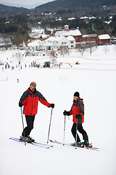 A man and woman pause on the slopes at the Quechee Ski Hill in Quechee, Vermont. Model Release.