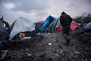 A man is seen walking in the Grande Synthe camp, partialy flooded, France. FEDERICO SCOPPA/CAPTA