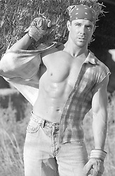 hot man with an open shirt carrying hay