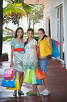 Three teenage girls (16-17) carrying shopping bags standing on street portrait