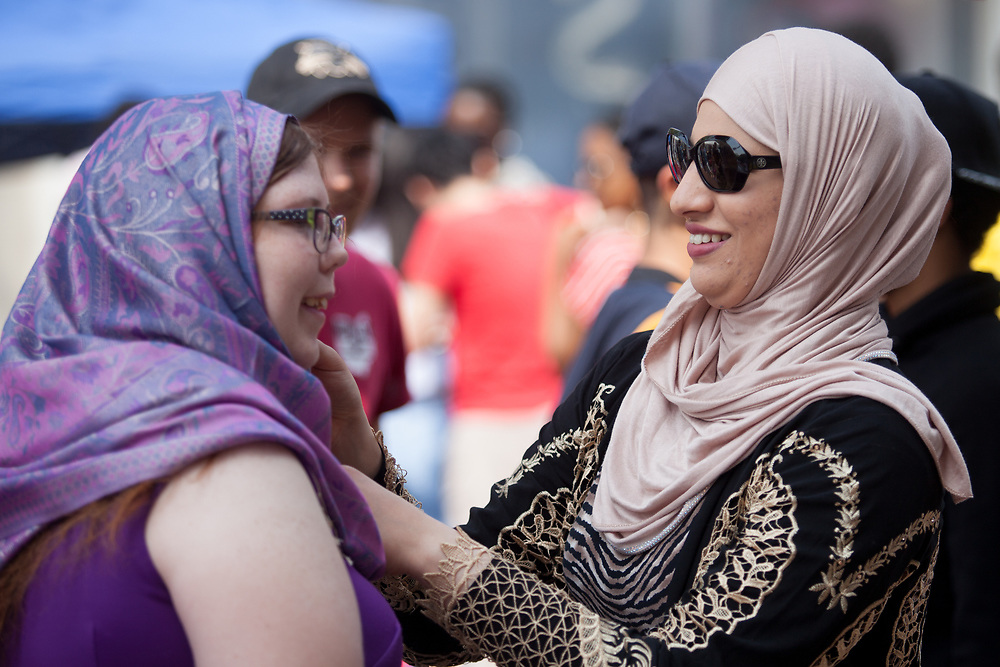 Basair Al-hinai helps Cheyenne Sears put on a hijab during the the International Street Fair on Saturday April 15, 2017. Photo by Kaitlin Owens