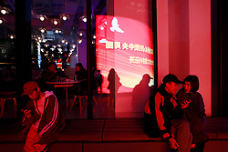 epa06267141 Young Chinese people sit in front of a window shop front reflecting a large electronic billboard showing propaganda for the coming 19th National Congress with the words 'Unite closely with comrade Xi Jinping as the core of the Communist Party, welcome with good results the successful opening of the 19th National Congress' outside a shopping complex in Beijing, China, 15 October 2017. The Communist Party of China (CPC) is making preparations for the five-yearly 19th National Congress scheduled to begin on 18 October. During the Congress, members will elect a new Central Committee, including a new 24-member Politburo and a new seven-member Standing Committee.  EPA-EFE/HOW HWEE YOUNG