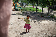A little girl in front of a sleeping dog in the Roma area of Frumusani.