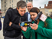 20 MAY 2019 - DAVENPORT, IOWA: BETO O'ROURKE looks at cell phone video of the flood that roared through downtown Davenport on April 30. O'Rourke, running to be the 2020 Democratic nominee for the US Presidency, has made climate change a central part of his campaign. He toured flood damage in Davenport Monday. The Mississippi River flooded through downtown Davenport on April 30 and much of downtown is still recovering from the flood.     PHOTO BY JACK KURTZ