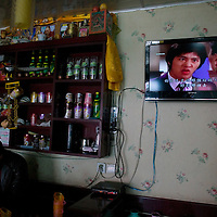 APRIL 4,2012 : a small picture of the Dalai Lama ( top Left) is isplayed near a TV screen in a Tibetan restaurant in Tongren .