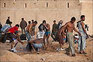 Des réfugiés font leur toilette au camp humanitaire Choucha situé à quelques kilomètres du poste frontière Ras Jedir. Plus de 140 000 réfugiés ont déjà quitté la Libye par la Tunisie ou l'Egypte et des milliers continuent d'arriver chaque jours. Vendredi 4 Mars 2011, Ras Jedir, Tunisie..© Benjamin Girette/IP3 press
