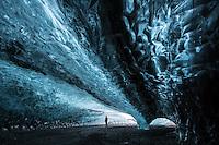 A photographer in an Ice Cave in Breiðármerkurjökull Glacier, Souteast Iceland.