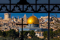 The Dome on the Rock on the Temple Mount, viewed through an ornate window with a cross in the Sanctuary of Dominus Flevit (Roman Catholic church) on the Mount of Olives, Jerusalem, Israel.