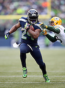 Seattle Seahawks running back Marshawn Lynch (24) runs away from a would be tackler for a 24 yard touchdown that, combined with a two point conversion, gives the Seahawks a 22-19 lead, their first of the day, during the NFL week 20 NFC Championship football game against the Green Bay Packers on Sunday, Jan. 18, 2015 in Seattle. The Seahawks won the game 28-22 in overtime. ©Paul Anthony Spinelli