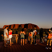 Tourists watching the sunrise in Uluru. Uluru (Ayers Rock or Red Rock) in Northern Territory. World Heritage Site, Uluru-Kata Tjuta National Parl is sacred to the Anangu, the Arboriginal People of the area.