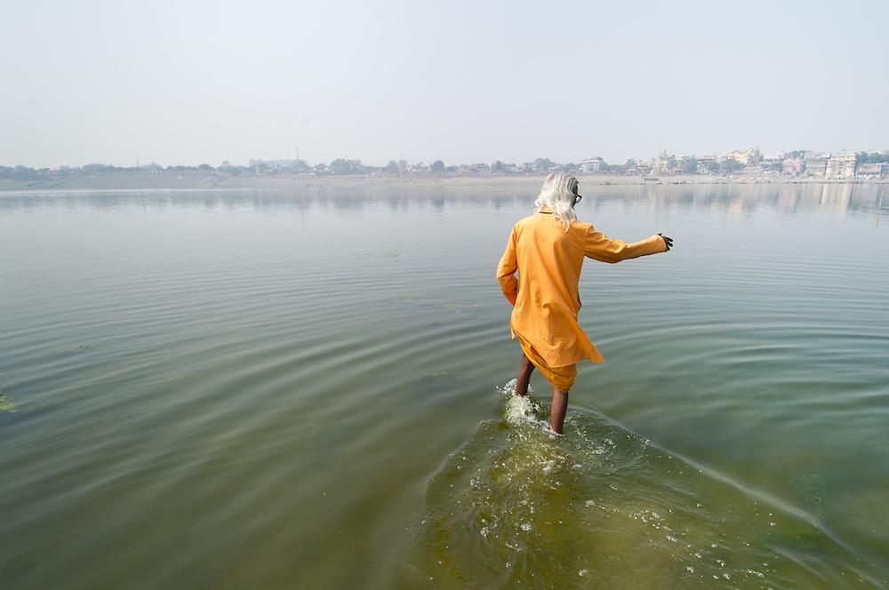 Man dressed in organge robe, walking into river Ganga in Varanasi (India)