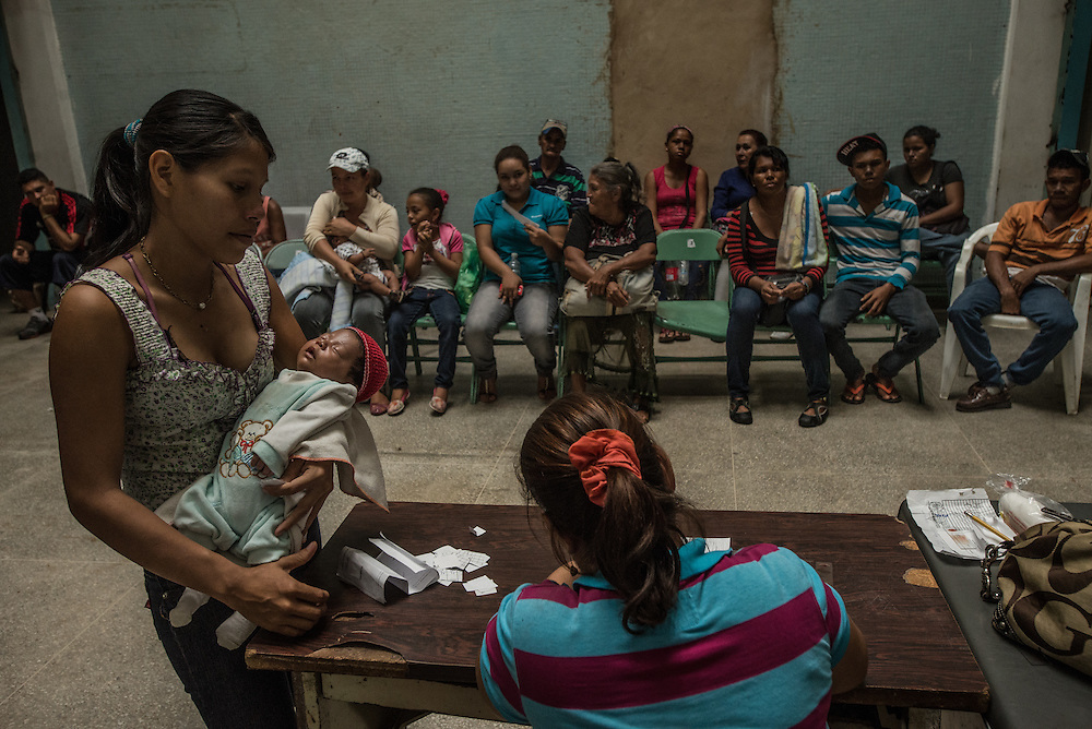 "SAN FELIX, VENEZUELA - MAY 24, 2016: Hundreds of people overflow a small clinic, all with symptoms of malaria: fevers, icy chills and uncontrollable tremors. A handful of doctors and hospital staff tried their best to test each patient for malaria: pricking their ears for a blood sample in a room without air conditioning and no lights because the government had cut power to save electricity. There were no medicines to be distributed, because the health ministry had not delivered any this day. Frustrated patients protested in the street outside of the hospital pleading for malaria medicine to be delivered.  Dr. Griselda Bello waved her hands helplessly to tell yet another patient that there was no medicine that day. ""Come back tomorrow at 10 a.m.,"" she said. ""My God,"" the patient said. ""Someone might die by then."" ""Indeed they might,"" she said. The spread of malaria in Venezuela is a state secret. Since 2007, the government has not submitted annual epidemiological reports on the disease and says there is no epidemic. But the most recent report, obtained by The New York Times from Venezuelan doctors involved in compiling it, confirms a surge is underway.  Last year, malaria cases rose 56% to 136,000 cases, the highest level in 75 years when the state began efforts to eradicate the disease, according to the report. Malaria has cut a wide swath through the country with cases now present in half of its 23 states. And among the strains present here is Plasmodim falciparum, the most fatal and severe form of the disease.   PHOTO: Meridith Kohut for The New York Times"