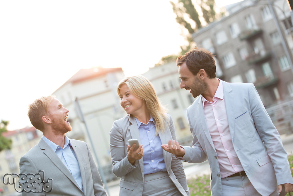 Cheerful businesspeople walking in city