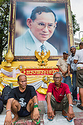 """11 MAY 2013 - BANGKOK, THAILAND:  Protesting farmers sit in front of a portrait of Bhumibol Adulyadej, the King of Thailand. Several hundred small scale family farmers camped out """"Government House"""" (the office of the Prime Minister) in Bangkok to Thai Prime Minister Yingluck Shinawatra to deliver on her promises to improve the situation of family farmers. The People's Movement for a Just Society (P-move) is a network organization which aims strengthen the voices of different, but related causes working to bring justice for marginalized groups in Thailand, including land rights for small-scale farmers, citizenship for stateless persons, fair compensation for communities forced to relocate to accommodate large scale state projects, and housing solutions for urban slum dwellers, among others.   PHOTO BY JACK KURTZ"""
