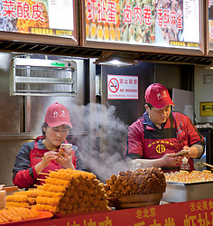 Night Market, Beijing, China. Two food vendors busy with their cell phones.