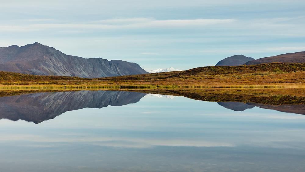 Reflection of Alaska Range Mountains on 17-mile Lake along the Denali Highway in Interior Alaska. Autumn. Morning.