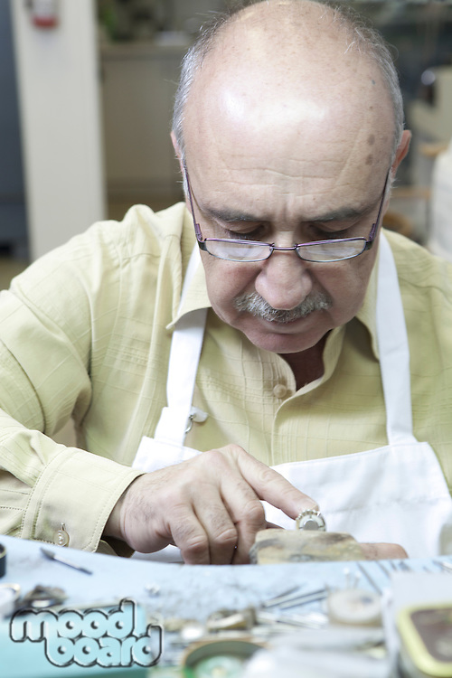Mature skilled worker concentrating on repairing ring in workshop