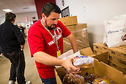 05 NOVEMBER 2013 - PHOENIX, AZ: PAUL BYLINOWSKI, a volunteer at St. Mary's Food Bank in Phoenix, AZ, packs carts for clients. Demand at St. Mary's has continued to increase even as government assistance is reduced. Over the summer, St. Mary's Phoenix location provided emergency food for 300 - 400 families per day. They are currently supporting about 600 families per day. Part of the increase is seasonal but a large part of it is no clients coming to the food bank for the first time. More than 1.1 million Arizonans who use the Supplemental Nutrition Assistance Program, known as food stamps, saw their benefits reduced Friday, Nov. 1, in a long-planned national cut that was tied to the economic stimulus which was a part of the American Recovery and Reinvestment Act. The cuts imposed last week range from $11 a month for a single recipient to $65 or more for large families. Many of SNAP receipients already use food banks to supplement their government assistance and the cuts in the SNAP program are expected to increase demand even more.   PHOTO BY JACK KURTZ