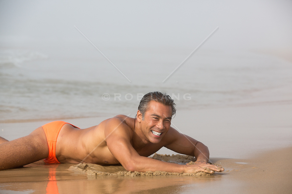 Asian American sexy man in a speedo at the ocean
