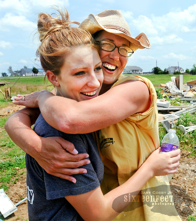 Daily Photo by Gary Cosby Jr...Robbie and Kim Stewart took delivery of their new mobile home Thursday replacing their house destroyed in the April 27 tornado.  Brittany Hare and her mom Kim Stewart hug one another as the new home is delivered.