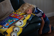 Lucas (5) sits next to his book at home in Shefield UK Tuesday, Aug. 12, 2014The D'Arby family is involved in the FAST  (Families and Schools Together) program which encourages parents to read to their children at home.(Elizabeth Dalziel for Save the Children )