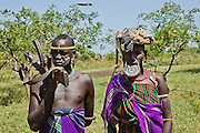 Mursi tribe couple the woman has a clay lip disc as body ornamentstribe the man is carrying a AK-47 Debub Omo Zone, Ethiopia. Close to the Sudanese border.