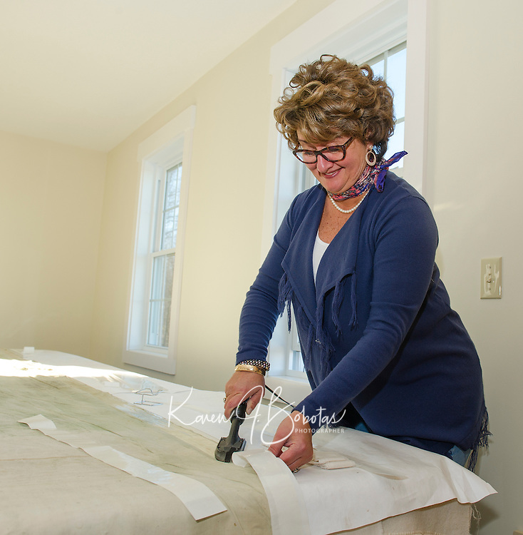 Laconia Historical Society Director Brenda Kean stabilizing the side margins of the Lakeport Opera House theater drape on Tuesday morning.  (Karen Bobotas/for the Laconia Daily Sun)