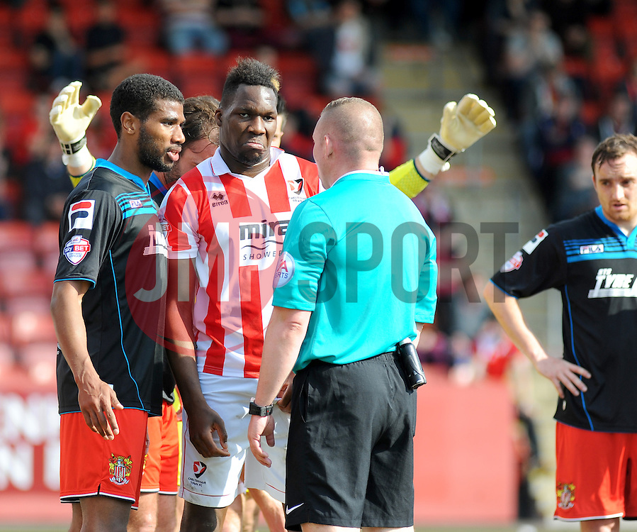 Referee Richards Clark has words with Cheltenham Town's Mathieu Manset and Stevenage's Jerome Okimo. - Photo mandatory by-line: Nizaam Jones - Mobile: 07966 386802 - 06/04/2015 - SPORT - Football - Cheltenham - Whaddon Road - Cheltenham Town v Stevenage - Sky Bet League Two