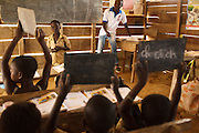 Children hold up their slates to show their answers during class at the Podio primary school in the village of Podio, Bas-Sassandra region, Cote d'Ivoire on Friday March 2, 2012.