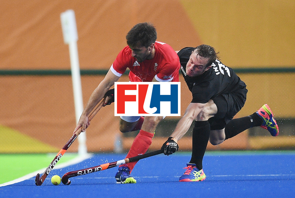 New Zealand's Hugo Inglis (R) and Britain's Adam Dixon stretch for the ball during the men's field hockey Britain vs New Zealand match of the Rio 2016 Olympics Games at the Olympic Hockey Centre in Rio de Janeiro on August, 7 2016. / AFP / MANAN VATSYAYANA        (Photo credit should read MANAN VATSYAYANA/AFP/Getty Images)