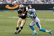 Adrian Peterson(28) stiff arms Thomas Davis(58) in the New Orleans Saints 34 to 13 victory over the Carolina Panthers.