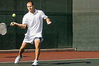 Tennis Player swinging tennis racket in forehand motion on tennis court