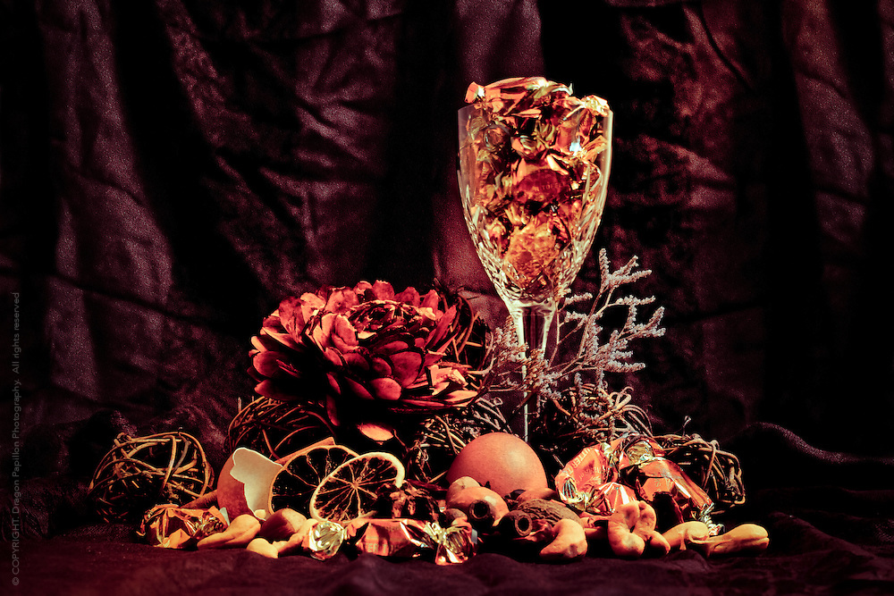 Still life composition in deep rich autumn tones showcasing a crystal wine glass, dried flowers, fruit and spices, borken egg shell and fudge wrapped in gold foil.