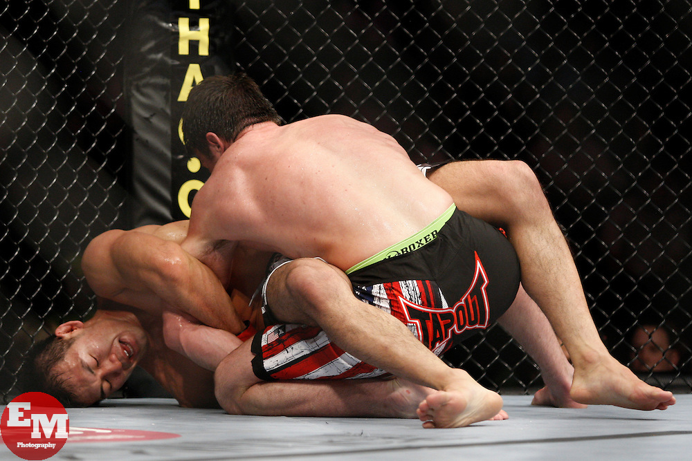 October 24, 2009; Los Angeles, CA; USA; Yushin Okami (white trunks) attempts a kimura on Chael Sonnen (black/flag trunks) during their bout at UFC 104.  Sonnen won via unanimous decision.  Mandatory Credit:  Ed Mulholland
