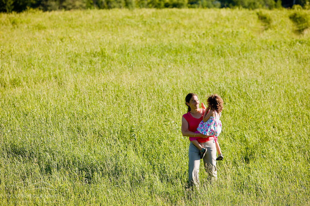 A mom and her young daughter walk in a field in Sabins Pasutre in Montpelier, Vermont.