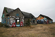 Blown-up portraits by photographer JR glued on houses at Pirou-Plage, Normandy