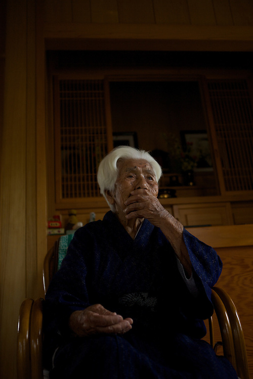 """We traveled to the town of Ogimi and tracked down its most famous inhabitant: Ushi Okushima. Over the past five years this 104-year-old woman has been filmed by every major news organization in the world, including the Discovery Channel, CNN, and the BBC. She's like the Dalai Lama of longevity. ..When we met Ushi, she sat queen-like and serene on a chair in front of a family altar for her ancestors. Wrapped in a blue kimono, she motioned for the team to sit down. Like kindergartners around their teacher, we sat cross-legged on the floor at her feet. And she greeted us by raising her arms above her head, as if to show off her biceps, and shouted, """"Genki! Genki! Genki!"""" or """"Vigor! Vigor! Vigor!"""" So many people fear getting old. If they could see this woman, they'd look forward to it. ..Ushi still wakes at 6 a.m., makes a breakfast of vegetable miso soup, and goes out for a stroll. Then every afternoon she eats lunch with her daughter, and her grand children and friends come over to visit. In the evenings she eats a dinner of mostly vegetables, drinks a cup of mugwort sake, and goes bed. What's her longevity secret? """"Work hard, drink mugwort sake before bed, and get a good night's sleep,"""" Ushi said. ..Actually, asking an old person how she got to be so old is like asking a tall person how she got so tall. They don't really know. But there her life does offer a few clues. For example, Ushi's day is full of social interaction. A Harvard study showed that the seniors with the most social ties were three times less likely to die during the study period than those who had the least social connections. So make time for your family and friends, and you just might add a few years to your life....------------------------------..Ushi Okishima is arguably the most famous centenarian in Okinawa and probably in the world. I met Ushi five years ago while doing an educational project on longevity. My co-leader at the time was a young educational manager by the name of Sayoko Ogata. ."""