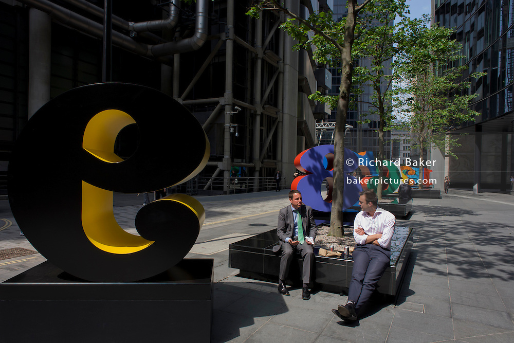 City workers rest by an art installation entitled 'One Through Zero (The Ten Numbers)' by American pop artist Robert Indiana (b 1928), in Lime Street, City of London, the capital's Square Mile, and its financial heart.